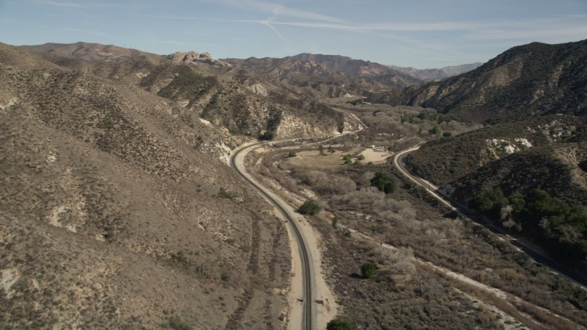 5K stock footage aerial video follow train tracks through mountainous countryside in Santa Clarita, California Aerial Stock Footage | AX0005_020