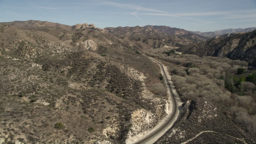 5K stock footage aerial video follow train tracks toward rock formation in Santa Clarita, California Aerial Stock Footage | AX0005_021