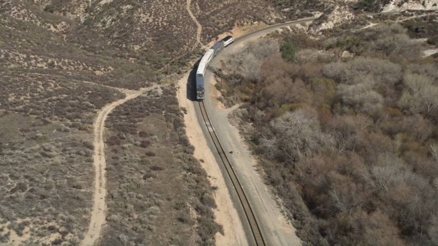 5K stock footage aerial video reveal and approach passenger train in Santa Clarita, California Aerial Stock Footage | AX0005_024