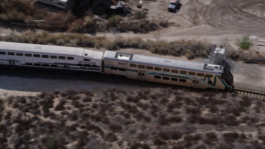 5K stock footage aerial video of tracking a Metrolink commuter train in the Santa Clarita Countryside in California Aerial Stock Footage | AX0005_026