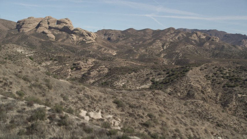 5K stock footage aerial video fly over a mountain ridge to reveal rock formation in the Mojave Desert, California Aerial Stock Footage AX0005_031 | Axiom Images