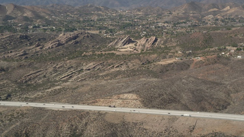 5K stock footage aerial video approach Vasquez Rocks Park from the freeway in the Mojave Desert, California Aerial Stock Footage | AX0005_036