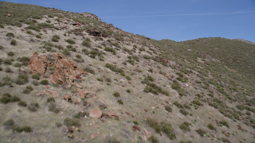 5K aerial video low altitude fly over of arid mountain slopes in the Mojave Desert, California Aerial Stock Footage | AX0005_052