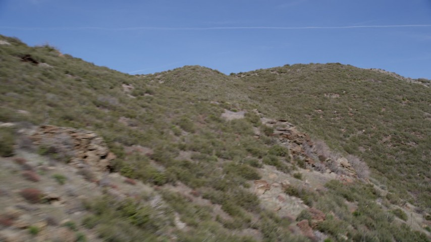 5K stock footage aerial video fly low over arid mountain slopes in the Mojave Desert, California Aerial Stock Footage | AX0005_053