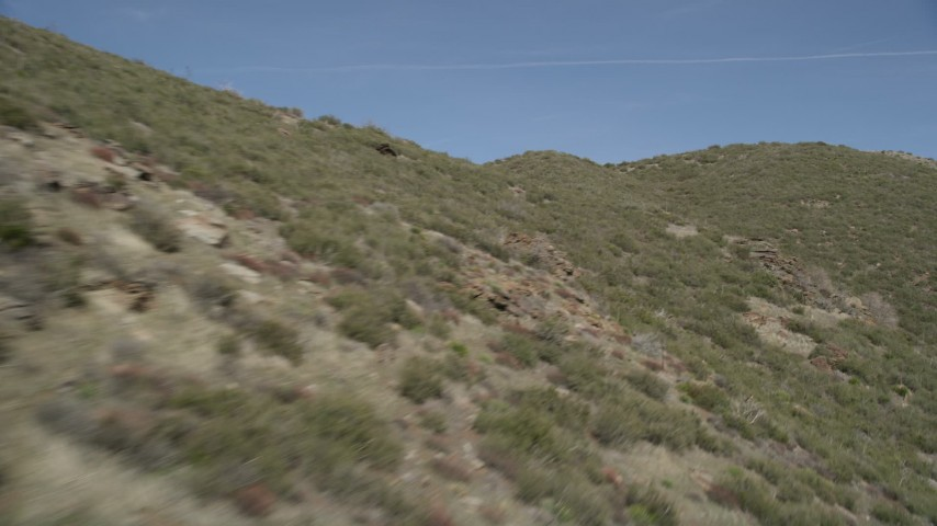 5K stock footage aerial video fly low over arid mountain slopes in the Mojave Desert, California Aerial Stock Footage | AX0005_053E