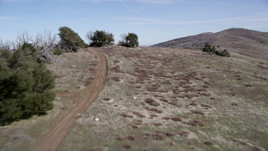 5K stock footage aerial video fly low over dirt roads and a mountain ridge in the Mojave Desert, California Aerial Stock Footage | AX0005_055