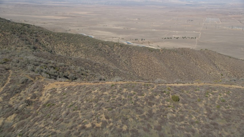 5K stock footage aerial video fly over mountain ridges to approach California Aqueduct in the Mojave Desert Aerial Stock Footage | AX0005_057E