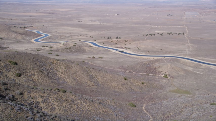 5K stock footage aerial video approach desert aqueduct from arid mountains in the Mojave Desert Aerial Stock Footage | AX0005_058