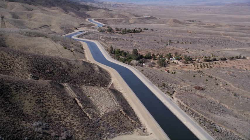 5K stock footage aerial video of following the California Aqueduct by mountains in Mojave Desert, California Aerial Stock Footage | AX0005_061