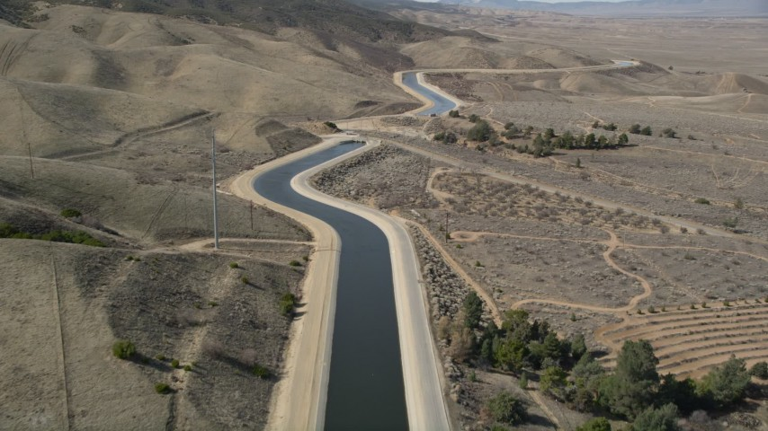 5K stock footage aerial video of following the California Aqueduct by mountains in Mojave Desert, California Aerial Stock Footage | AX0005_061E