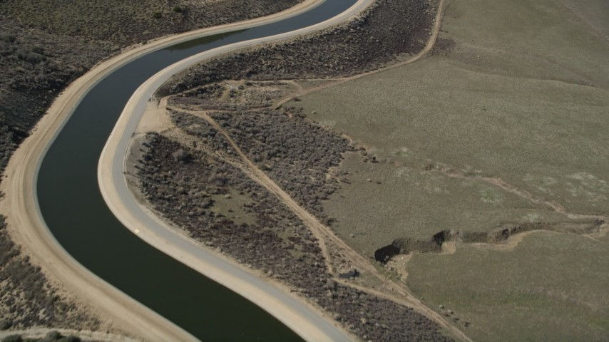 5K stock footage aerial video fly over the curves in a desert aqueduct in the Mojave Desert of California Aerial Stock Footage | AX0005_064