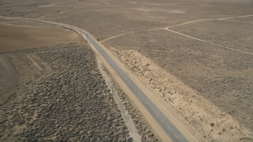 5K aerial video orbit desert road and white car in Antelope Valley, California Aerial Stock Footage | AX0005_067