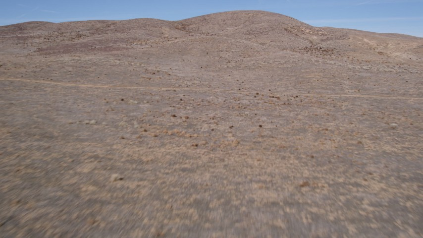 5K stock footage aerial video fly low over open desert toward arid hills in Antelope Valley, California Aerial Stock Footage | AX0005_069
