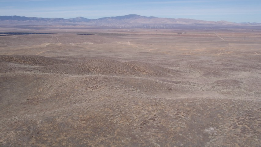 5K stock footage aerial video fly over small desert hills toward solar energy array in Antelope Valley Aerial Stock Footage | AX0005_071