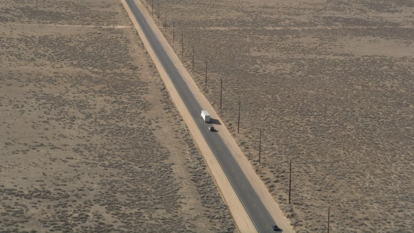 5K stock footage aerial video orbit a big rig and SUV on a desert road in Antelope Valley Aerial Stock Footage | AX0005_075