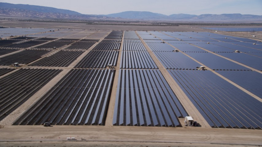 5K stock footage aerial video flying by panels at a solar farm in the desert of Antelope Valley, California Aerial Stock Footage | AX0005_082