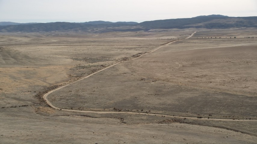 5K stock footage aerial video orbit a dirt road through the desert in Antelope Valley, California Aerial Stock Footage | AX0005_098