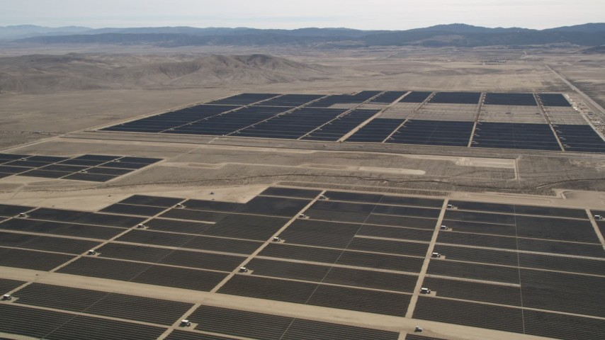 5K stock footage aerial video fly over solar panels to a second group of panels at a desert array in Antelope Valley, California Aerial Stock Footage | AX0005_109