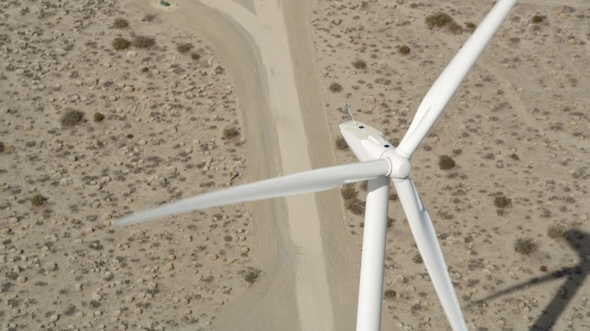5K stock footage aerial video fly over blades of a windmill in the Mojave Desert, California Aerial Stock Footage | AX0005_134