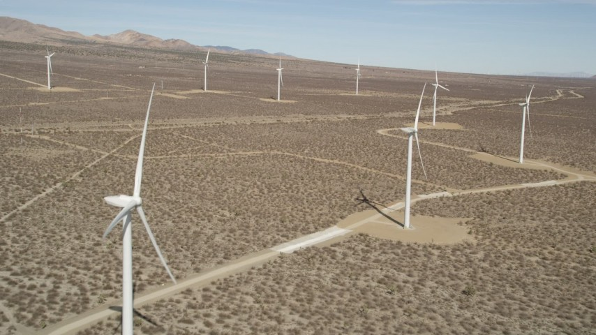 5K stock footage aerial video fly over a row of windmills at a desert wind farm in California Aerial Stock Footage   AX0005_139
