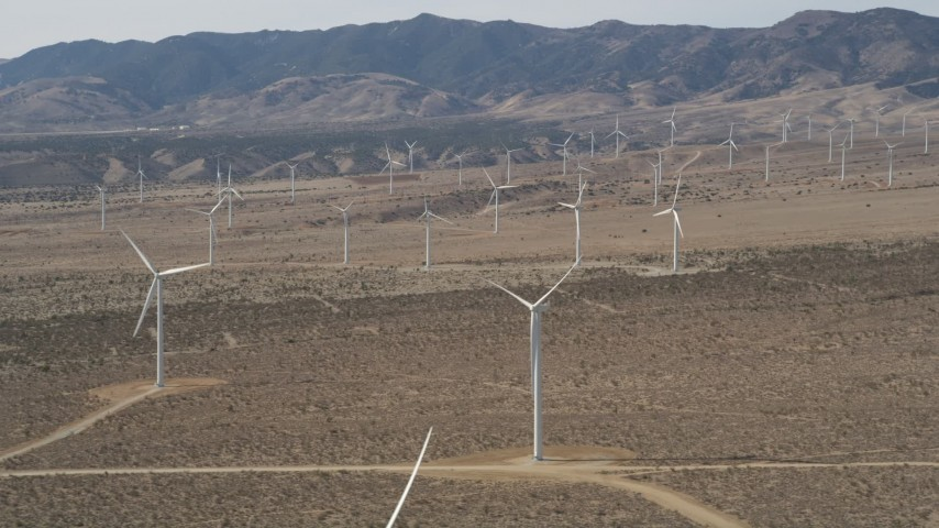 5K stock footage aerial video orbit a large group of windmills in the Mojave Desert of California Aerial Stock Footage   AX0005_143