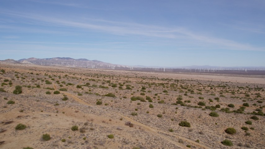 5K stock footage aerial video fly over desert plants toward wind farm in Antelope Valley, California Aerial Stock Footage | AX0006_004