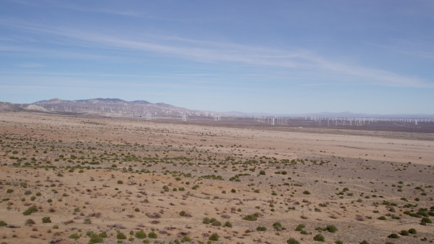 5K stock footage aerial video fly over desert vegetation toward a distant wind farm in Antelope Valley, California Aerial Stock Footage | AX0006_005