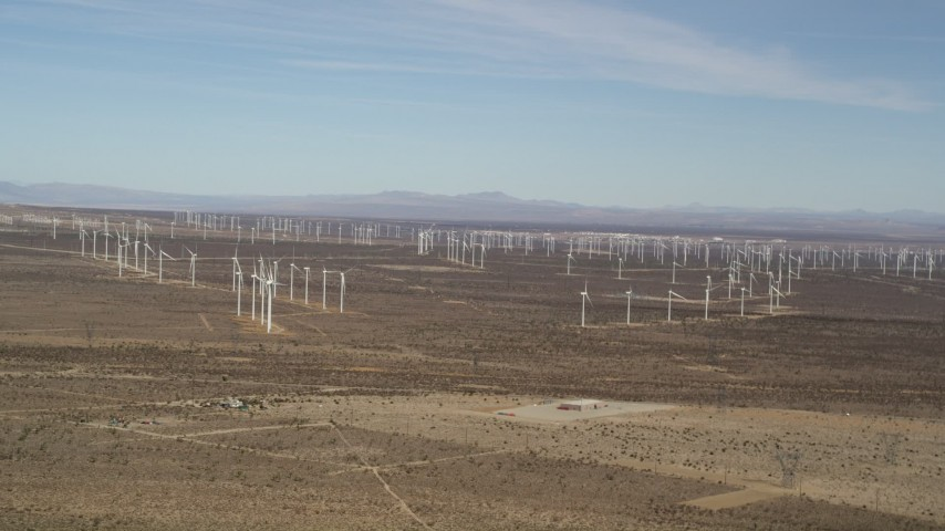 5K stock footage aerial video pan across rows of windmills at desert wind farm in Antelope Valley, California Aerial Stock Footage | AX0006_006