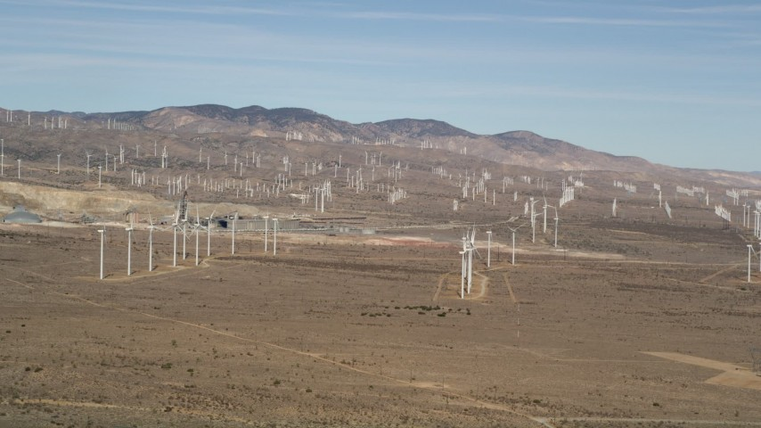 5K stock footage aerial video pan to a row of windmills at a large desert wind farm in Antelope Valley, California Aerial Stock Footage | AX0006_007