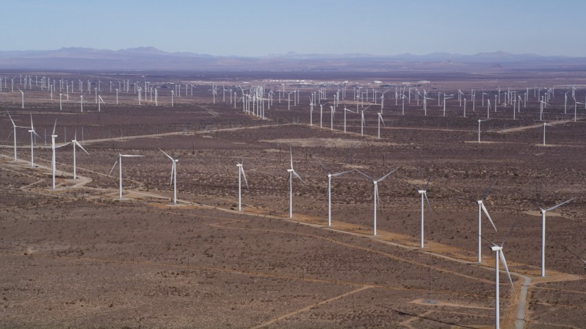 5K stock footage aerial video pan to line of windmills at large wind farm in the Mojave Desert, California Aerial Stock Footage | AX0006_008