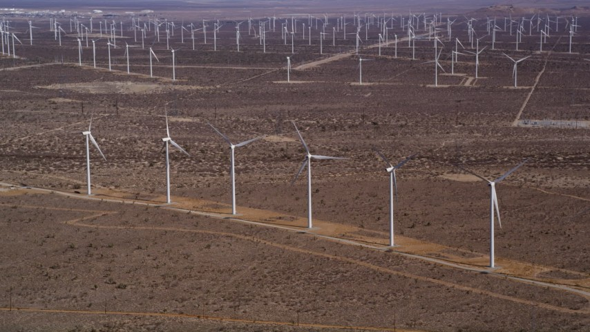 5K stock footage aerial video approach windmills at a wind energy farm in the Mojave Desert, California Aerial Stock Footage | AX0006_009