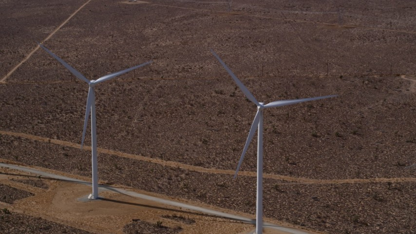 5K stock footage aerial video of a reverse view of a pair of windmills at a desert wind farm in California Aerial Stock Footage   AX0006_012