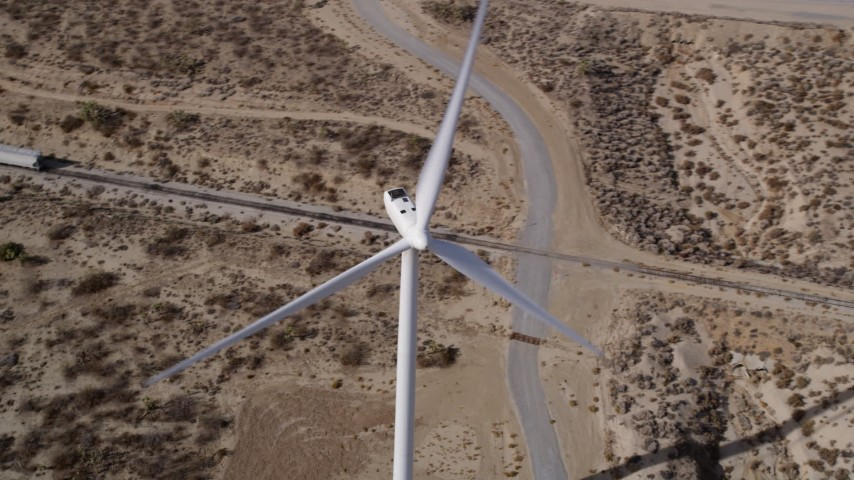 5K stock footage aerial video orbiting a lone windmill at a desert wind farm in Antelope Valley. California Aerial Stock Footage | AX0006_017