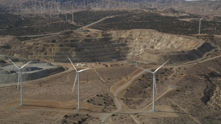 5K stock footage aerial video pan across windmills near a quarry in the desert, Antelope Valley, California Aerial Stock Footage | AX0006_018