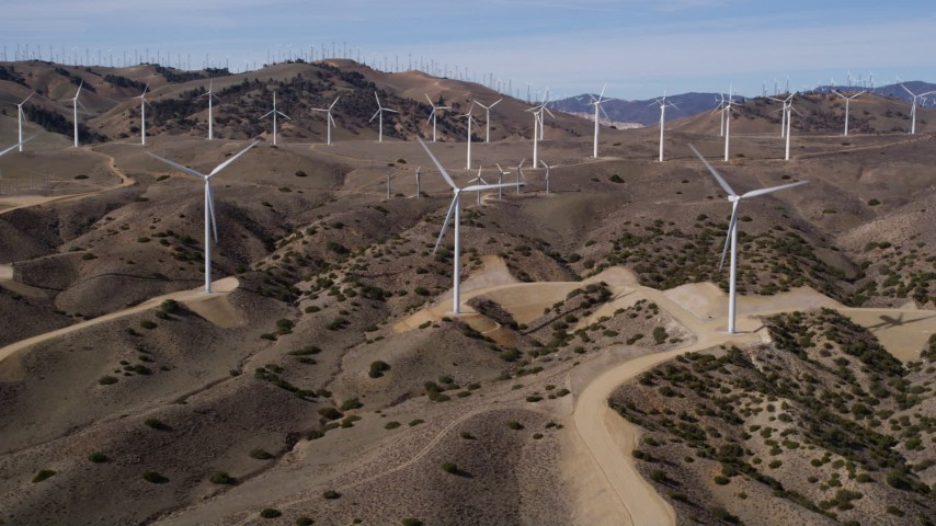 5K stock footage aerial video approaching a pair of windmills at a wind energy farm in the Mojave Desert of California Aerial Stock Footage | AX0006_023