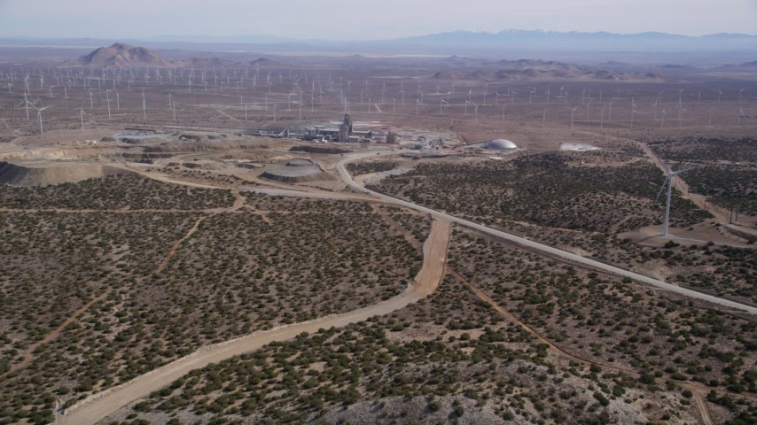 5K stock footage aerial video approach quarry surrounded by wind farm windmills in the Mojave Desert, California Aerial Stock Footage | AX0006_029