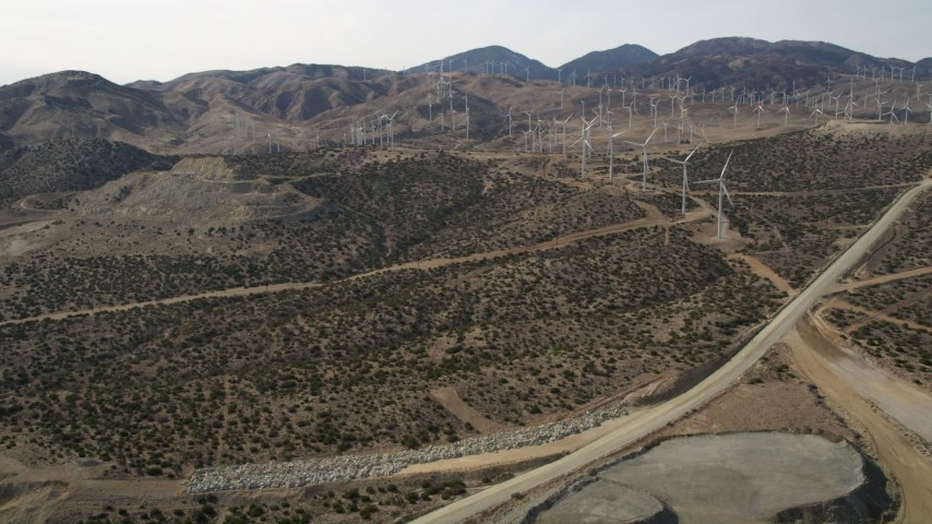5K stock footage aerial video fly over quarry pit to reveal desert wind farm in Antelope Valley, California Aerial Stock Footage | AX0006_036
