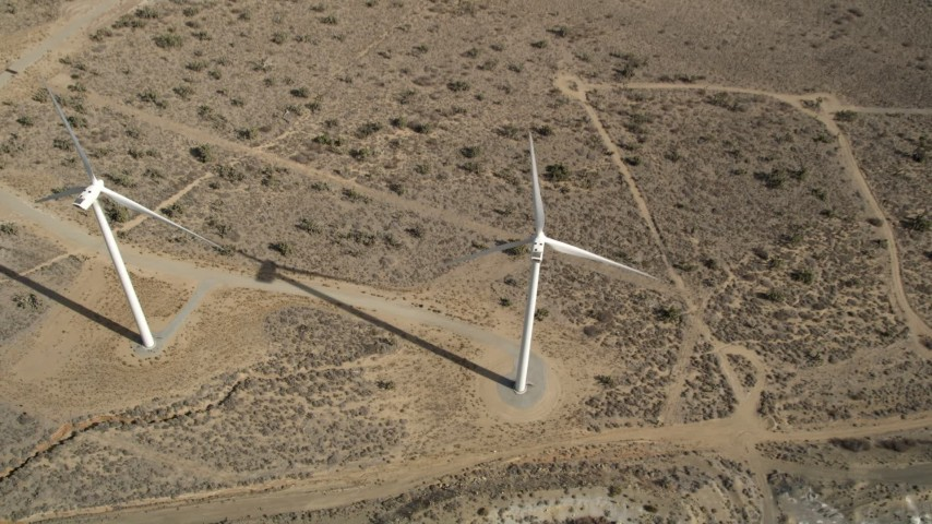 5K stock footage aerial video tilt to a bird's eye view of a pair of windmills in the Mojave Desert, California Aerial Stock Footage | AX0006_040