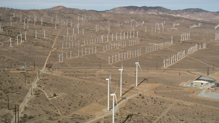 5K stock footage aerial video of a wide orbit around rows of windmills at a desert wind energy farm in California Aerial Stock Footage | AX0006_042