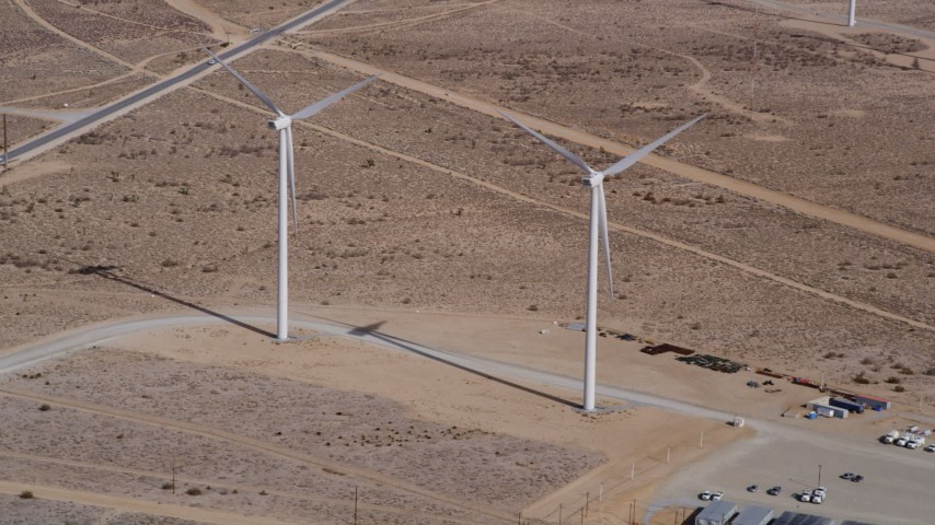 5K stock footage aerial video approach a couple of windmills at a desert wind energy farm in California Aerial Stock Footage | AX0006_046