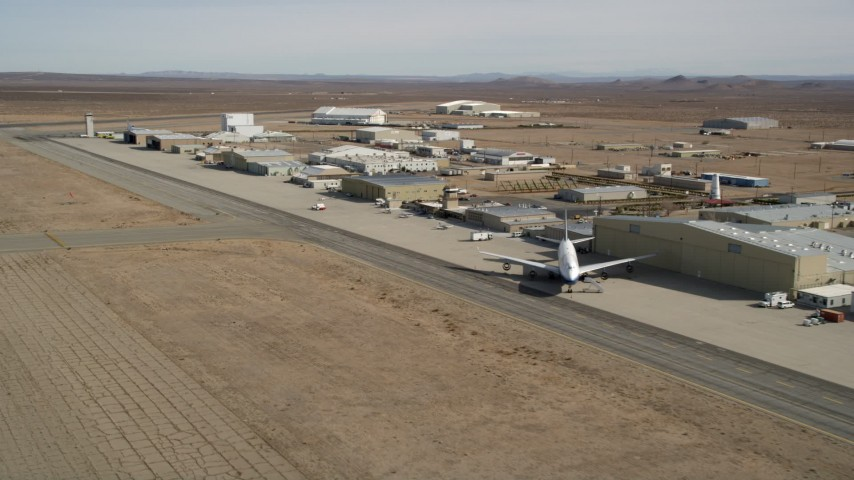5K stock footage aerial video pan to airliner by hangar at Mojave Air and Space Port in California Aerial Stock Footage | AX0006_055E