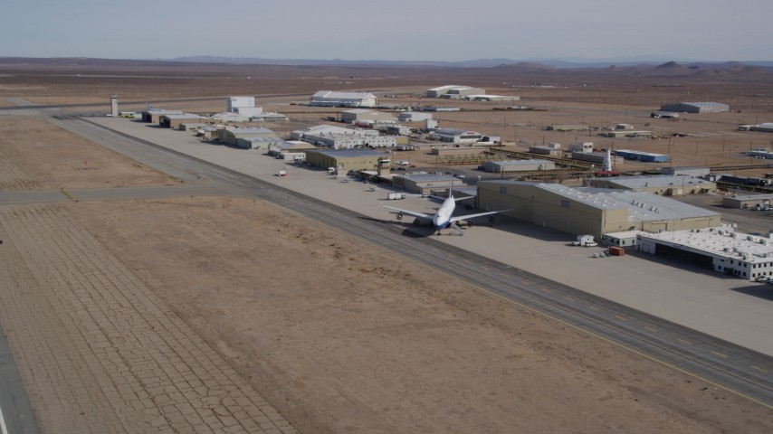 5K stock footage aerial video of passing a row of hangars at the Mojave Air and Space Port in California Aerial Stock Footage | AX0006_056