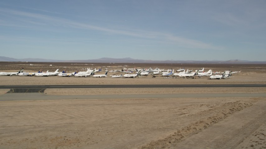 5K stock footage aerial video of a low altitude orbit of planes at an aircraft boneyard in the desert, Mojave Air and Space Port, California Aerial Stock Footage | AX0006_057