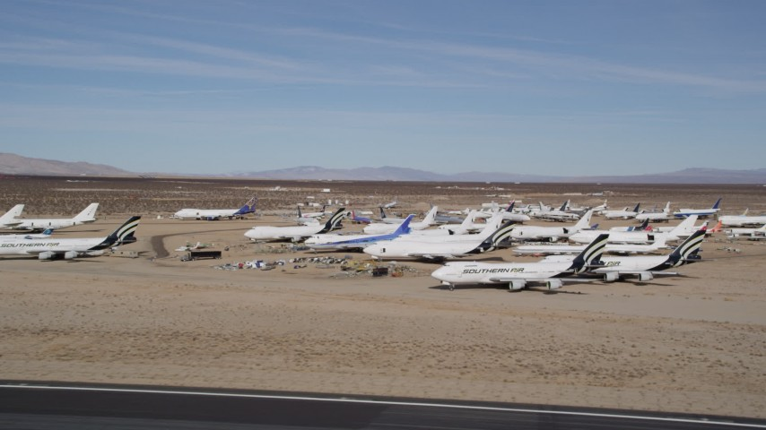 5K stock footage aerial video orbit low around various jet airplanes at an aircraft boneyard in the desert, Mojave Air and Space Port, California Aerial Stock Footage AX0006_058