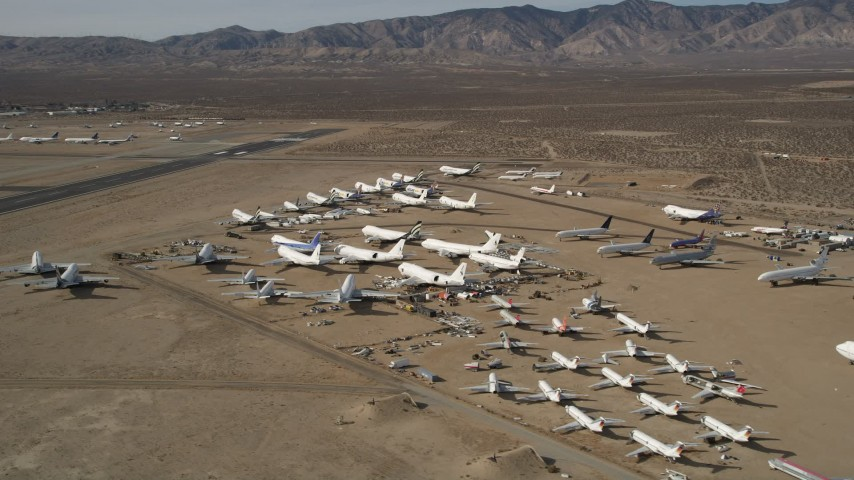 5K stock footage aerial video orbit low around various jet airplanes at an aircraft boneyard in the desert, Mojave Air and Space Port, California Aerial Stock Footage | AX0006_058E