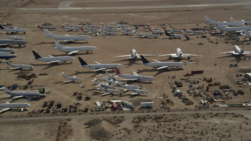 5K stock footage aerial video orbiting jet aircraft at an airplane boneyard in the Mojave Desert, California Aerial Stock Footage | AX0006_063
