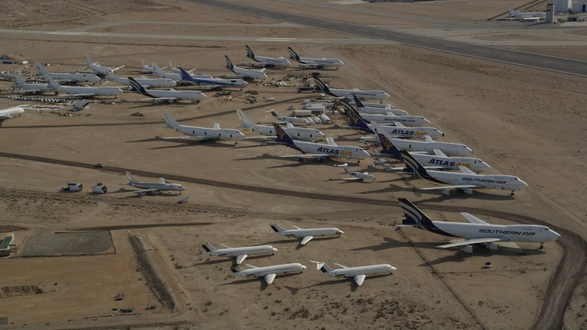 5K stock footage aerial video orbit a group of aircraft at a boneyard in the Mojave Desert, California Aerial Stock Footage | AX0006_064E
