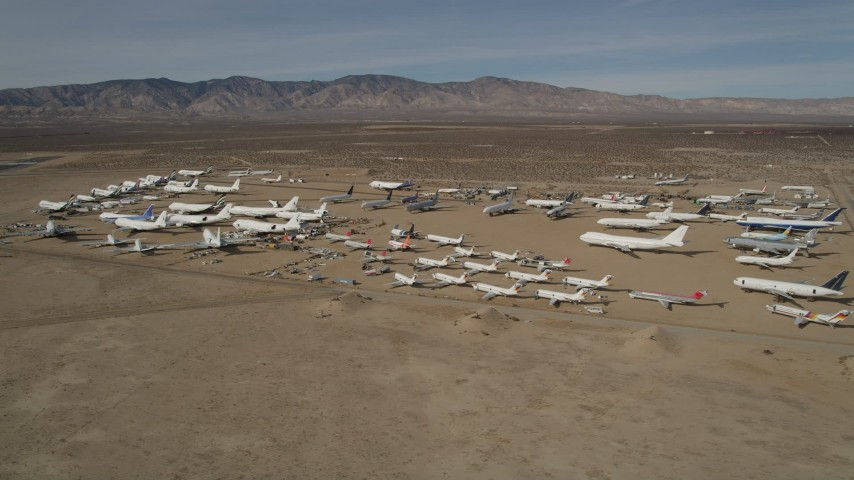 5K aerial video orbit airplanes in a desert field at an aircraft boneyard, Mojave Air and Space Port, California Aerial Stock Footage | AX0006_069