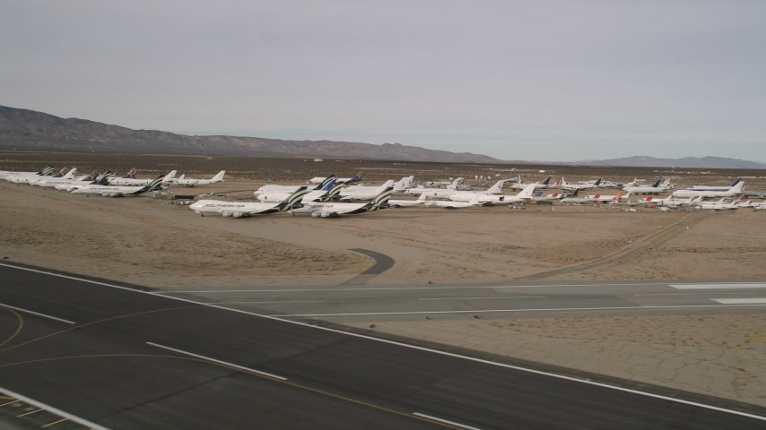 5K stock footage aerial video of flyby jet airplanes in a desert field at a California boneyard, Mojave Air and Space Port Aerial Stock Footage | AX0006_071