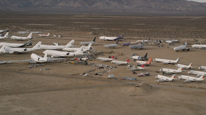 5K stock footage aerial video orbit large and small jets at a desert aircraft boneyard in Mojave Air and Space Port, California  Aerial Stock Footage | AX0006_072